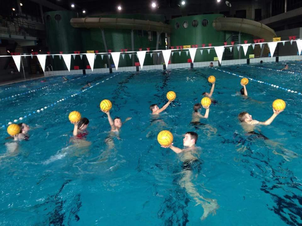 Competitiezwemmers met een waterpolobal